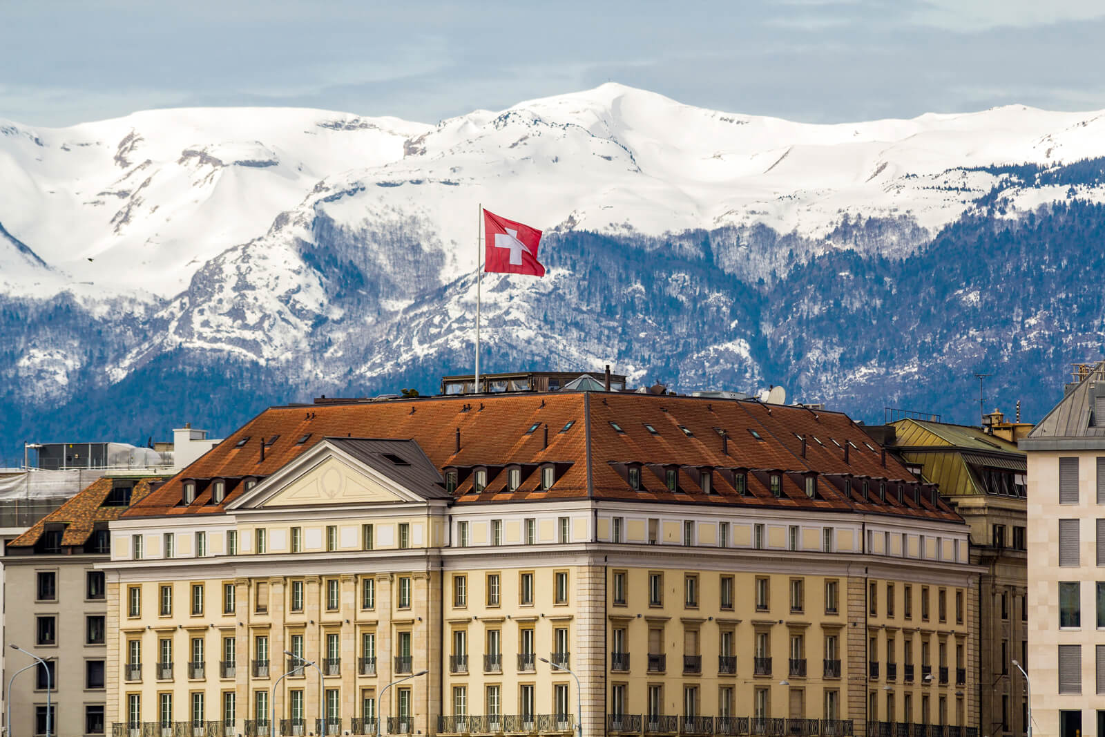 The Geneva City Scape with Snow-Covered Peaks and a Swiss Flag