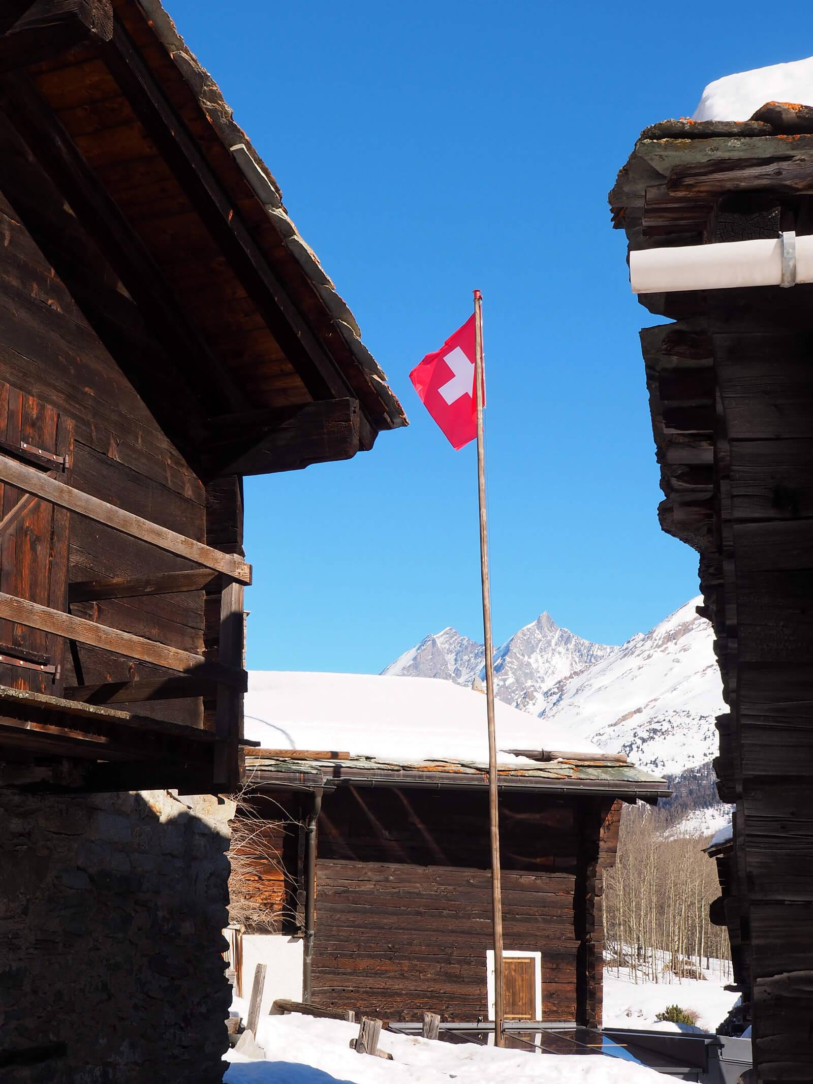 Cờ Thụy Sĩ trong một ngôi làng có tuyết phủ ở Valais, Thụy Sĩ