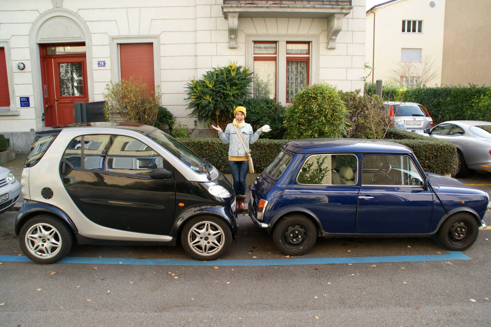 Two small cars parked bumper to bumper in Switzerland